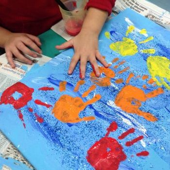 Programa asistencial: manos niño pintando