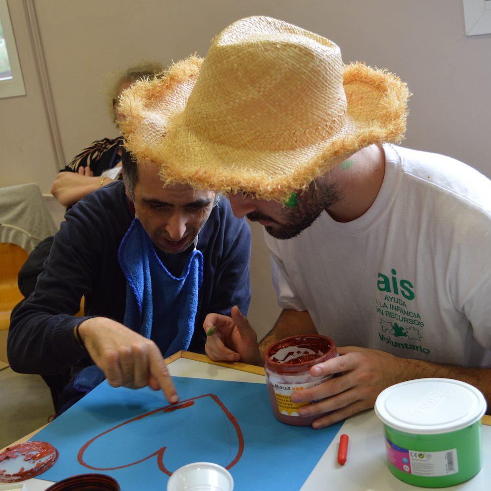 Programa voluntariado: voluntario y adulto pintando un corazón